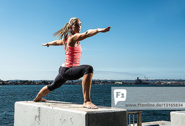 Frau praktiziert Yoga auf Betonklotz