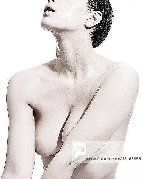 Nackte Frau mit Flüssigkeitströpfchen auf der Haut
