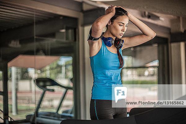 Junge Frau ruht sich im Fitnessstudio aus