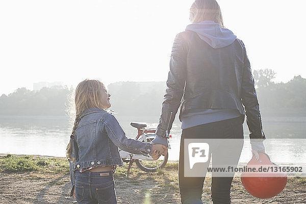 Mutter und Tochter  Händchen haltend  am See  Rückansicht