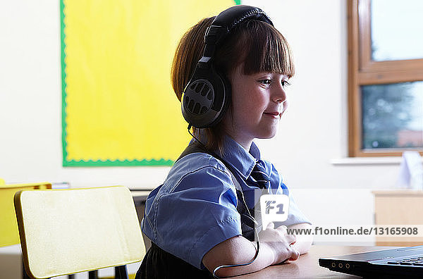 School girl wearing headphones and looking at computer in classroom