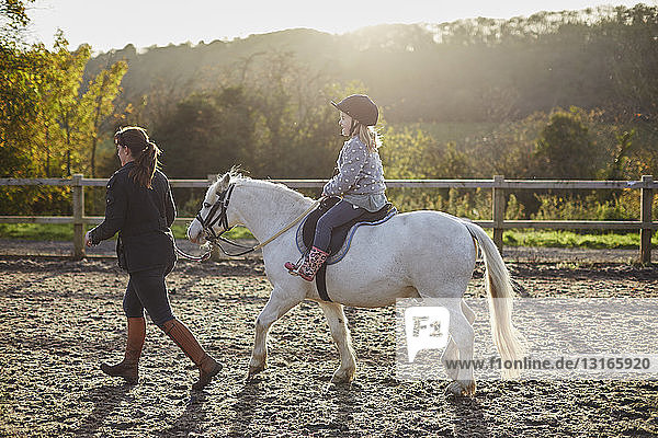 Instructor leading girl riding white pony in equestrian arena