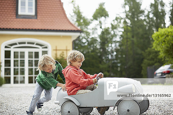 Two boys playing with vintage toy car in front of house