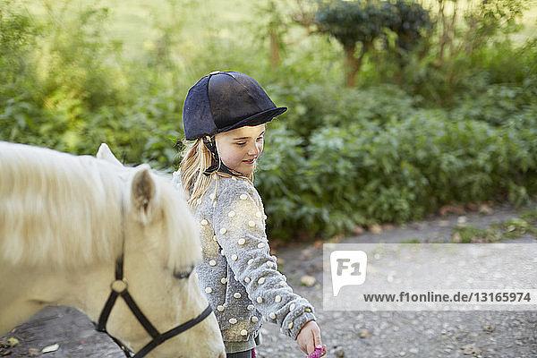 Girl leading white pony on rural road