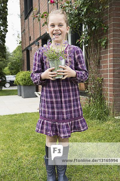 Portrait of girl with flower pot plant in garden