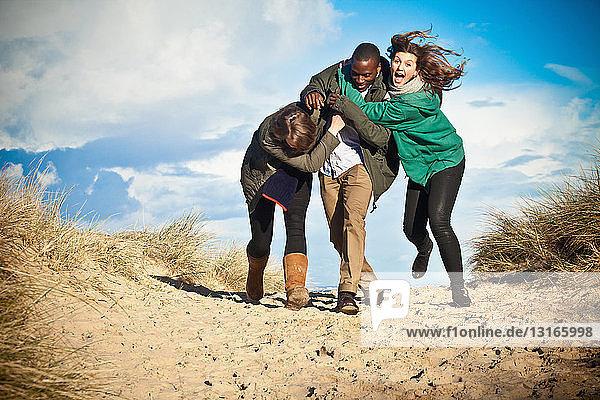 Junge erwachsene Freunde laufen in Sanddünen  Bournemouth  Dorset  UK