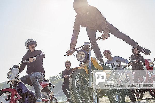 Eine Gruppe von Freunden fährt mit Mopeds die Straße entlang  ein Mann in der Luft  macht einen Stunt