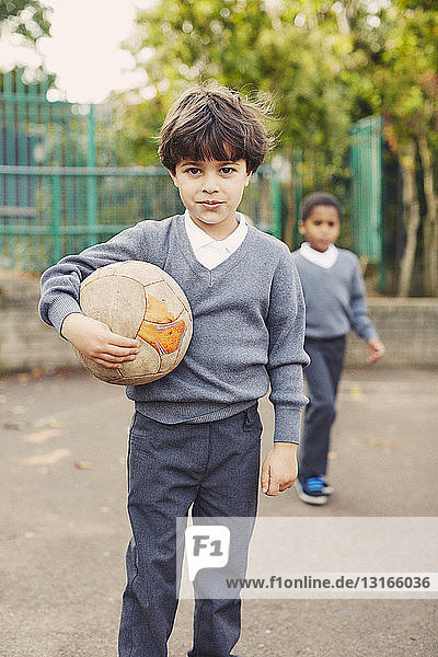 Portrait of elementary schoolboy holding soccer ball in playground
