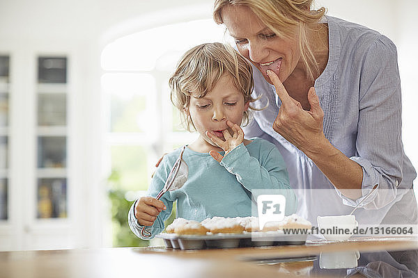 Mutter und Sohn backen Cupcakes in der Küche