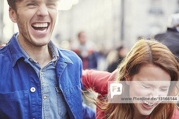 Couple laughing on street  London  UK