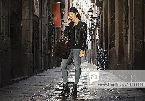 Frau chattet mit Smartphone in einer engen Straße  El Born  Barcelona  Spanien