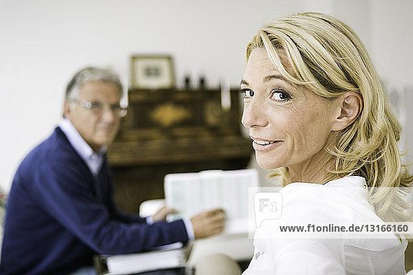 Frau in Besprechung schaut über die Schulter in die Kamera und lächelt