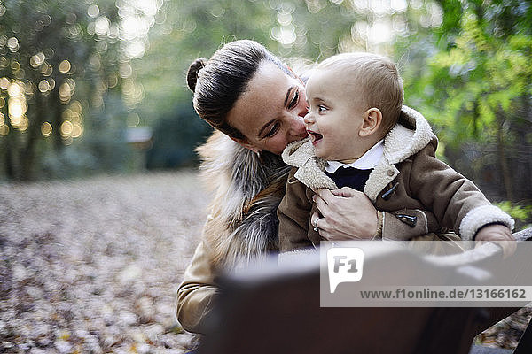 Mother holding male toddler on woodland park bench