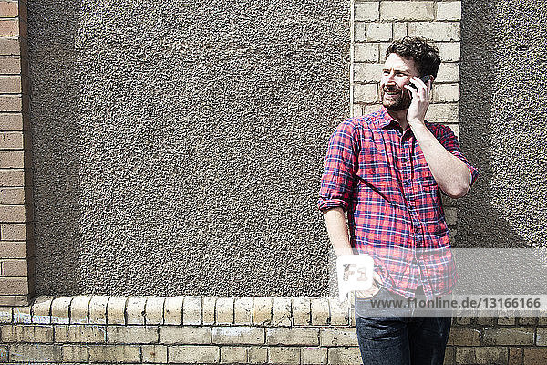 Young man leaning against wall chatting on smartphone