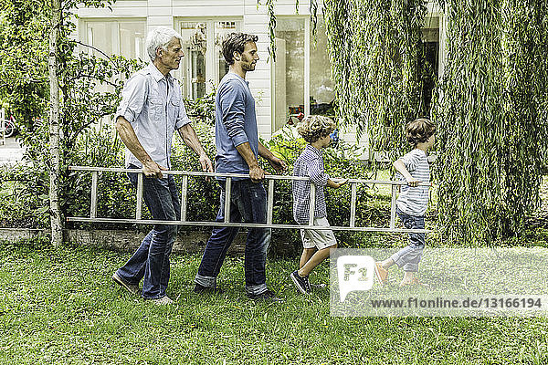 Erwachsener Mann mit Sohn trägt Leiter mit Enkeln im Garten