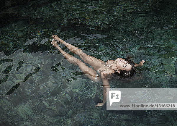 Young woman wearing bikini floating in sea