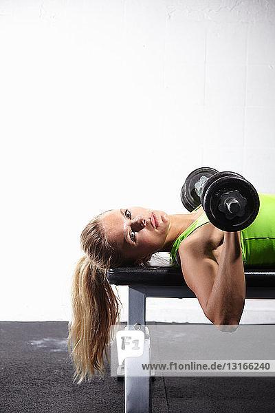 Junge Frau liegt auf Bank und trainiert mit Stangenglocke im Fitnessstudio