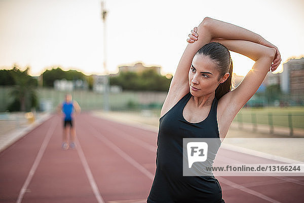 Junge Frau streckt Arm auf Laufbahn