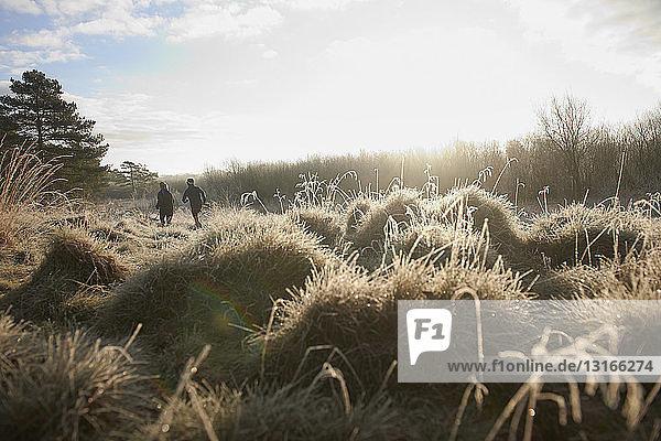 Rückansicht von Mutter und Sohn beim Laufen auf Grasland