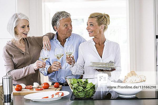 Glückliches älteres Ehepaar und reife Frau erheben in der Küche ein Glas Wein zueinander