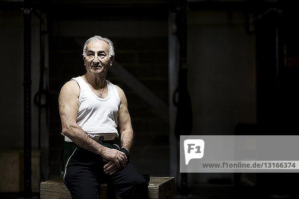 Portrait of grey haired senior man sitting in dark gym