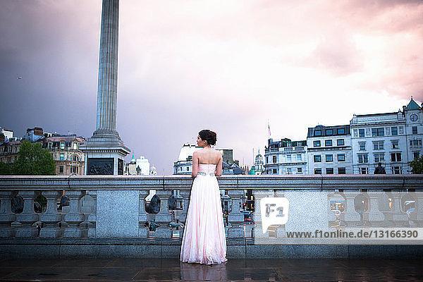 Junge Frau im Abendkleid in der Abenddämmerung  Trafalgar Square  London  Großbritannien