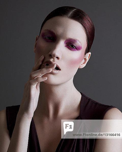 Porträt einer jungen Frau mit schwerem Augen-Make-up  die Hand berührt das Gesicht