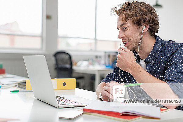 Young office worker using laptop and earphones at desk