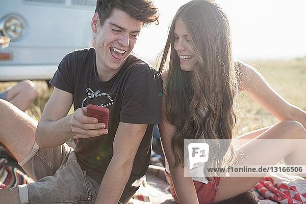 Junges Paar sitzt mit Smartphone im Freien