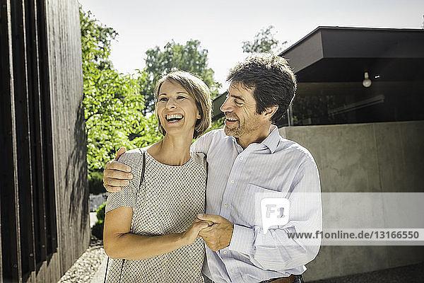 Glückliches reifes Paar vor neuem Haus