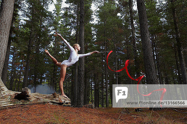 Dancer twirling ribbon in forest