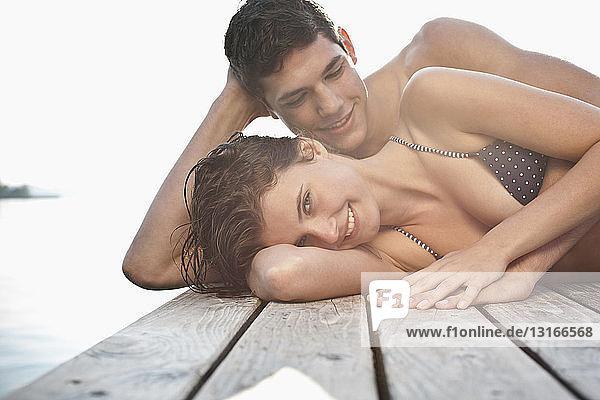 Porträt eines jungen Paares  das nebeneinander auf dem Steg liegt