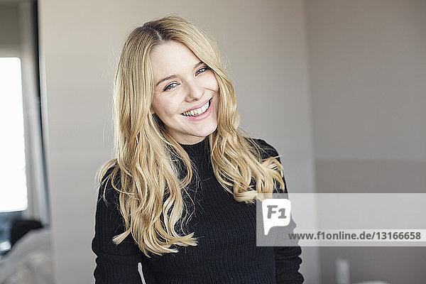 Porträt einer lächelnden jungen Frau im Schlafzimmer