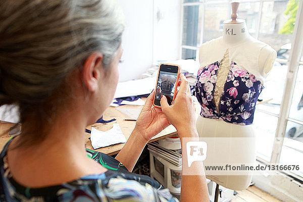 Designerin beim Fotografieren ihrer Kreation im Atelier