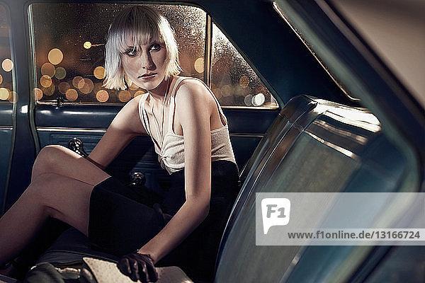 Frau sitzt auf dem Rücksitz eines Autos