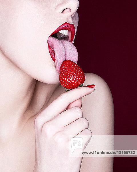 Frau leckt Erdbeere