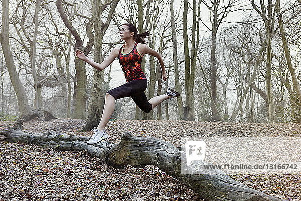 Young woman jumping over log in forest