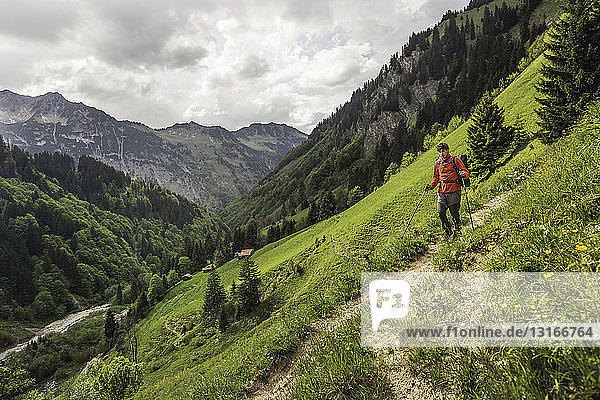 Young man hiking on valley path  Oberstdorf  Bavaria  Germany
