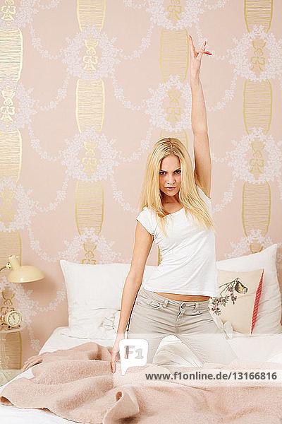 Auf dem Bett posierende Frau