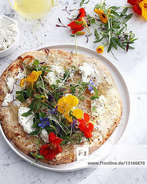 Pizzateller mit Käse und Blumen