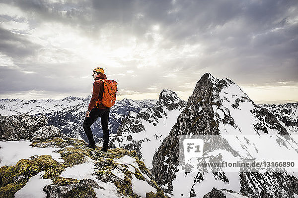 Rear view of hiker looking at snow capped mountain range  Kellenspitze  Tannheim mountains  Tyrol  Austria