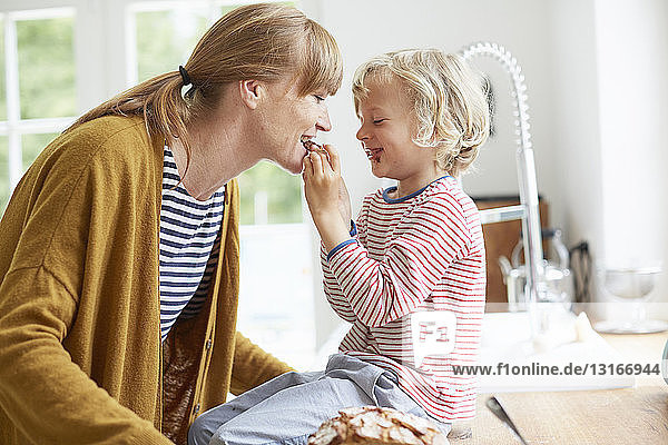 Young boy feeding mother a sweet treat