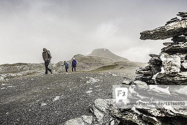 Männliche und weibliche Wanderer wandern durch eine düstere Landschaft  Fil de Cassons  Segnesboden  Graubünden  Schweiz