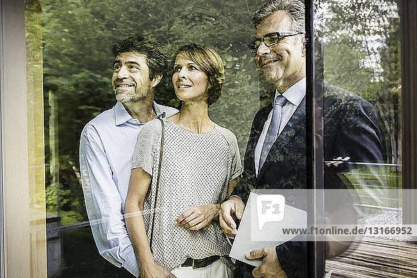 Immobilienmakler mit reifem Ehepaar schaut durch das Fenster eines neuen Hauses