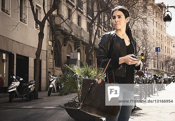 Woman using smartphone on street  El Born  Barcelona  Spain