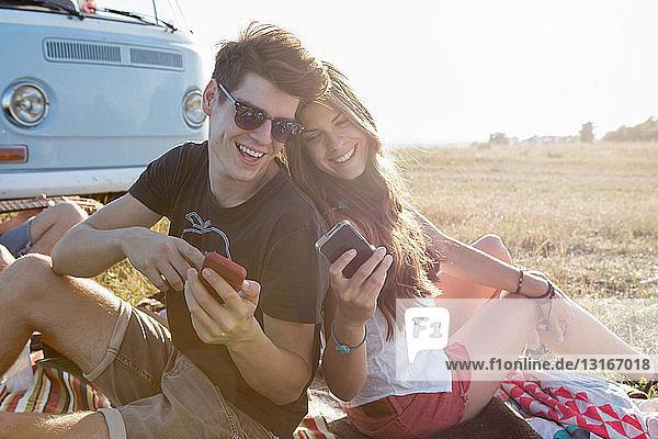 Junges Paar betrachtet Smartphones