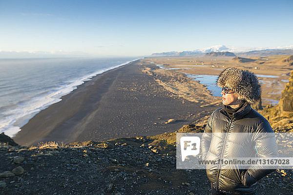 Reife Frau genießt Aussicht in Strandnähe  Island