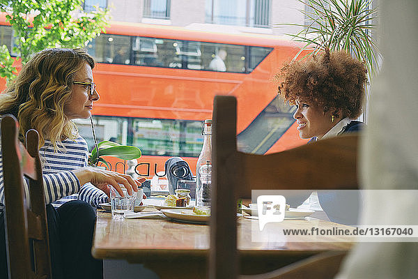 Two women friends eating lunch and chatting in cafe