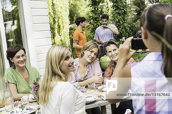 Junges Mädchen fotografiert eine Gruppe von Freunden beim Grillen