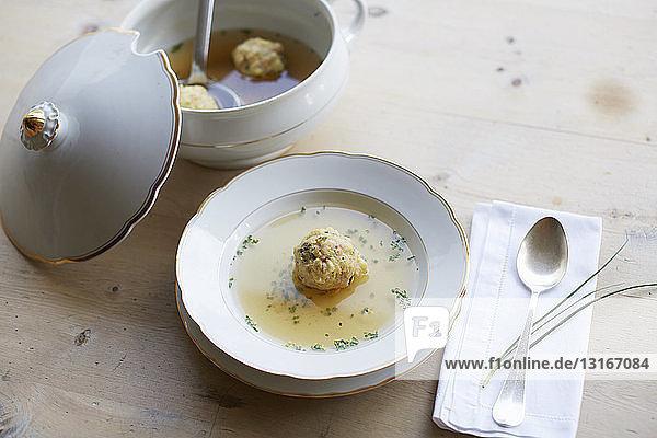 Tisch mit frischer Suppe und Knödel in einer Schüssel